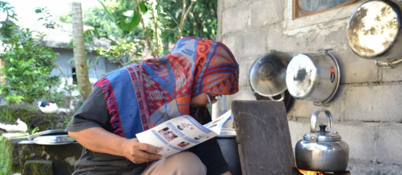 Woman learning to use clean cookstove