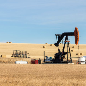 An oil pump jack in a farm field in Alberta, Canada.