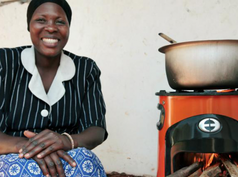 Woman uses a clean cookstove in Uganda