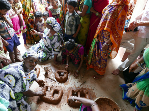 Women from Notarpali village teaching RUWES women how to make improved clay stoves