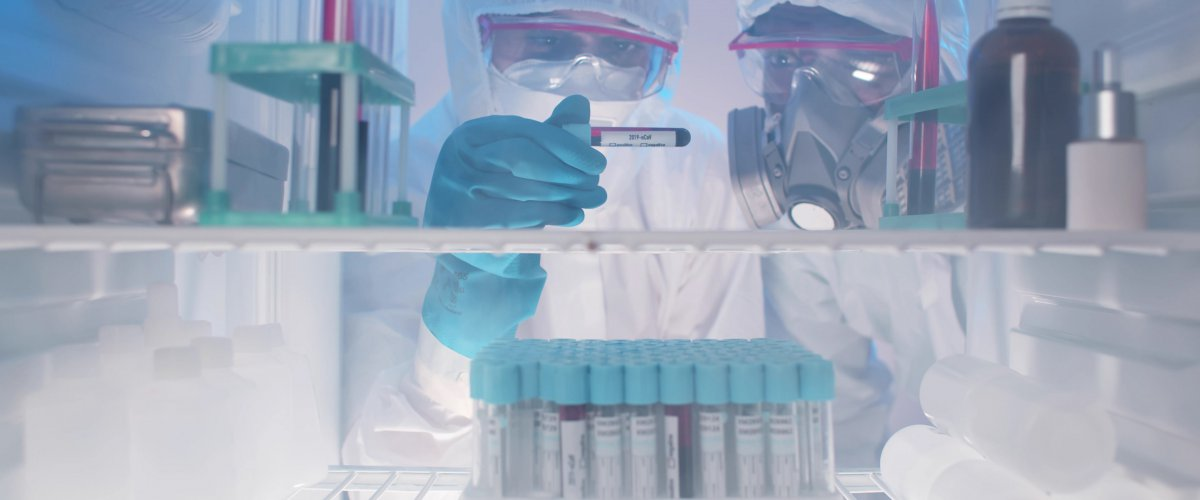 Laboratory workers examining covid-19 blood sample from fridge
