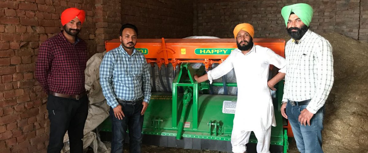 Farmers pose with a Happy Seeder in Punjab, India